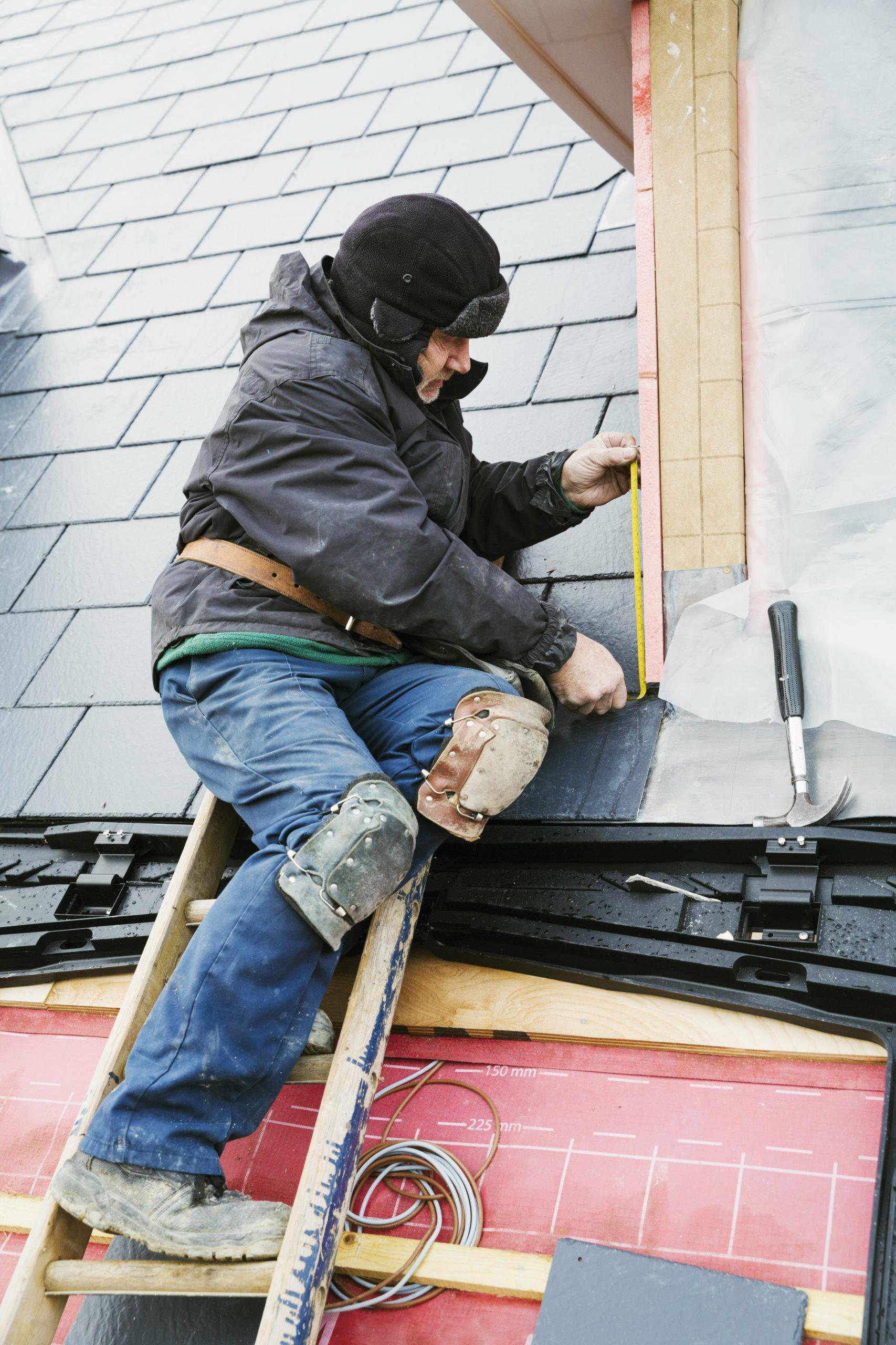 man fixing shingles