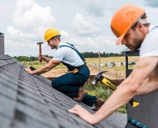 selective focus of handsome handyman repairing roof