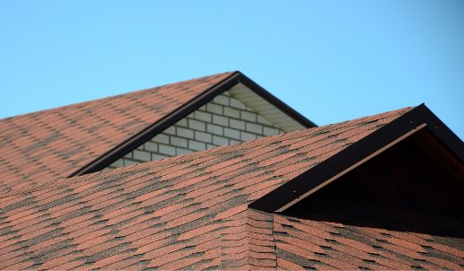 New red bitumen shingles on a light blue sky